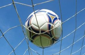 Perspective shot of soccer net with ball against clear blue sky
